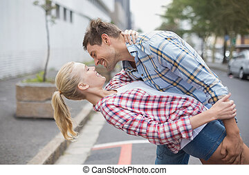 Hip romantic couple dancing in the street on a sunny day in...