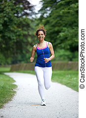Woman running on footpath in the park - Young woman running...
