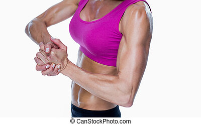 Female bodybuilder posing with hands together on white...