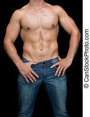 Muscular man posing shirtless in blue jeans on black...