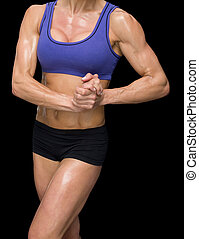 Female bodybuilder posing with hands together on black...