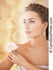 young woman with rose flower - bride and wedding concept -...