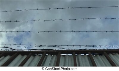 Fence with barbed wire - Camcorder moves next to a fence...