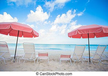 Chairs and umbrellas on stunning tropical beach