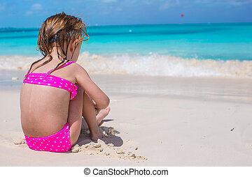 Back view of adorable little girl in swimsuit at tropical...