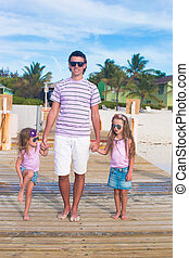 Family of three on wooden jetty by the ocean