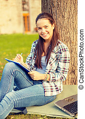 smiling teenager writing in notebook - education, campus and...