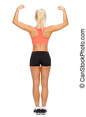 sporty woman from the back flexing her biceps - fitness,...
