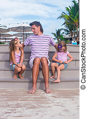 Family of three sitting on beach enjoying ocean view