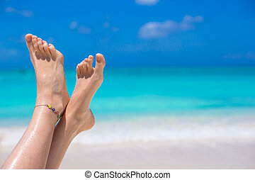 Close up of female legs on white sandy beach - Close up of...