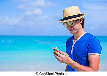 Young happy businessman with his phone on beach vacation -...