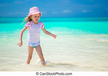 Adorable toddler girl playing in shallow water at exotic...