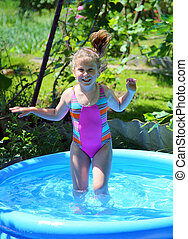 cheerful girl in inflatable pool in summer