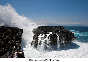 Ocean waves crushing against cliff