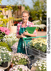 Garden center woman put potted flowers cart - Garden center...