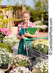 Garden center woman put potted flowers cart - Garden center...