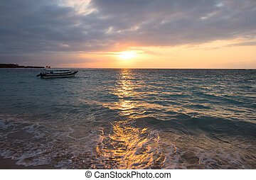 Calm ocean with boat during tropical sunrise