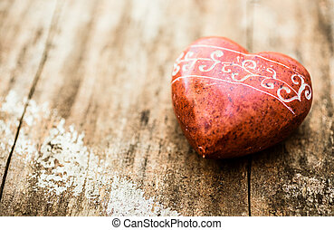 Red stone shaped like a heart with carvings on a wooden...