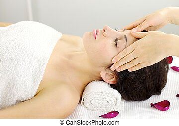 Relaxed woman getting head massage in spa during vacation