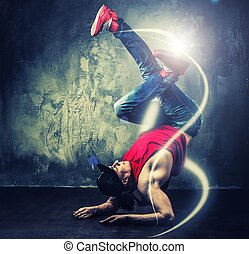 Stylish man dancer showing break-dancing moves with magic...