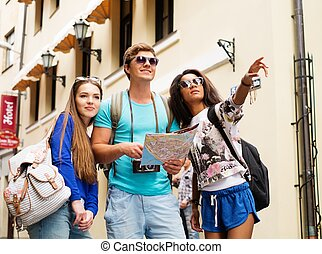 Multi-ethnic friends tourists with map in old city