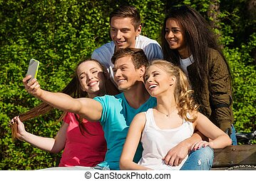 Multi ethnic group of sporty teenage friends in a park...