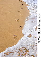 Footprints on beach sand and surging wave