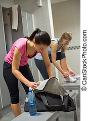 Woman packing bag at gym's locker room with friend in...