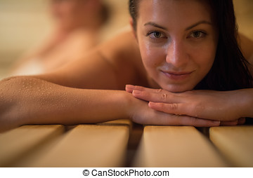 Woman lying on wooden bench at sauna - Closeup of young...