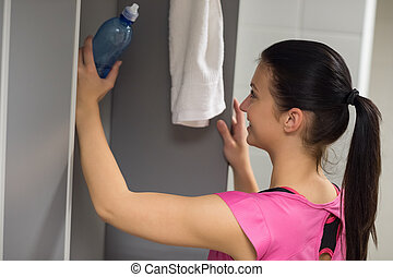 Woman putting bottle in locker at gym - Young woman putting...