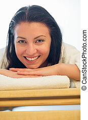 Smiling woman resting on bed at spa