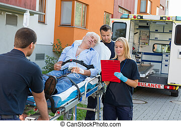 Emergency team assisting injured man on stretcher -...