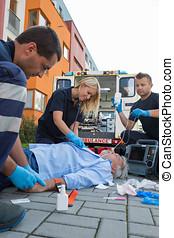 Emergency team helping injured elderly patient