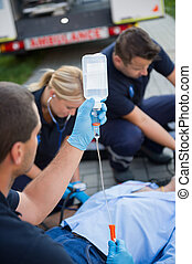 Paramedic team preparing drip for injured patient lying on...