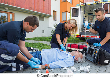 Paramedics giving firstaid to unconscious patient -...