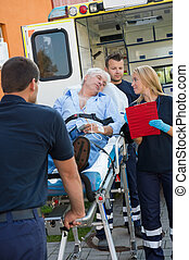 Paramedical team helping injured man on stretcher -...