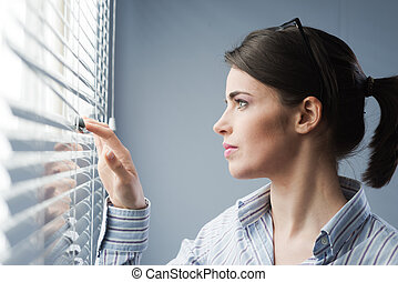 Attractive woman peeking through blinds - Young attractive...