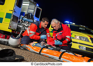 Paramedics giving firstaid to motorbike driver - Paramedics...