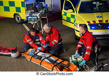 Paramedics helping motorbike driver on stretcher -...