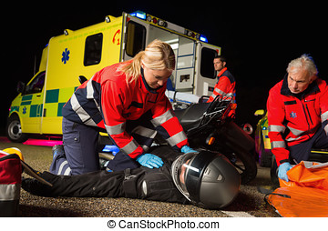 Paramedical team assisting injured motorbike driver -...