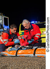 Paramedic team giving firstaid to injured woman at night