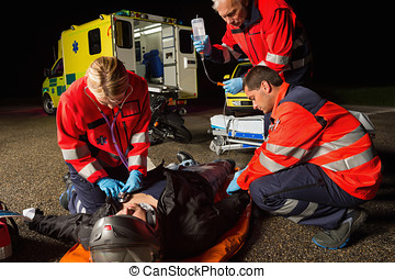 Emergency team helping injured motorbike driver - Emergency...