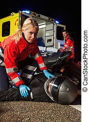Paramedic assisting motorbike driver at night - Paramedic...