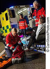 Paramedic team assisting injured motorbike driver -...