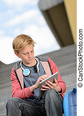 Student boy using tablet sitting on steps