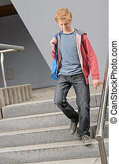 Student boy walking down university stairs