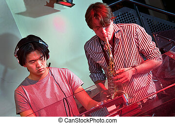 DJ and Saxophonist - DJ and saxophoneist jamming together in...