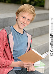 Happy teenage boy studying sitting on stairs