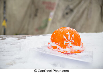 Orange hard hat. - Orange hard hat on snow with national...