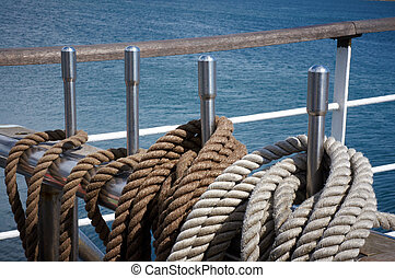 Rope control the sails, tied to a wooden beam, on sailboat